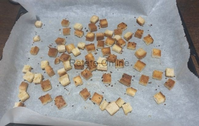 Introdu tava cu bucatelele de paine in cuptor
